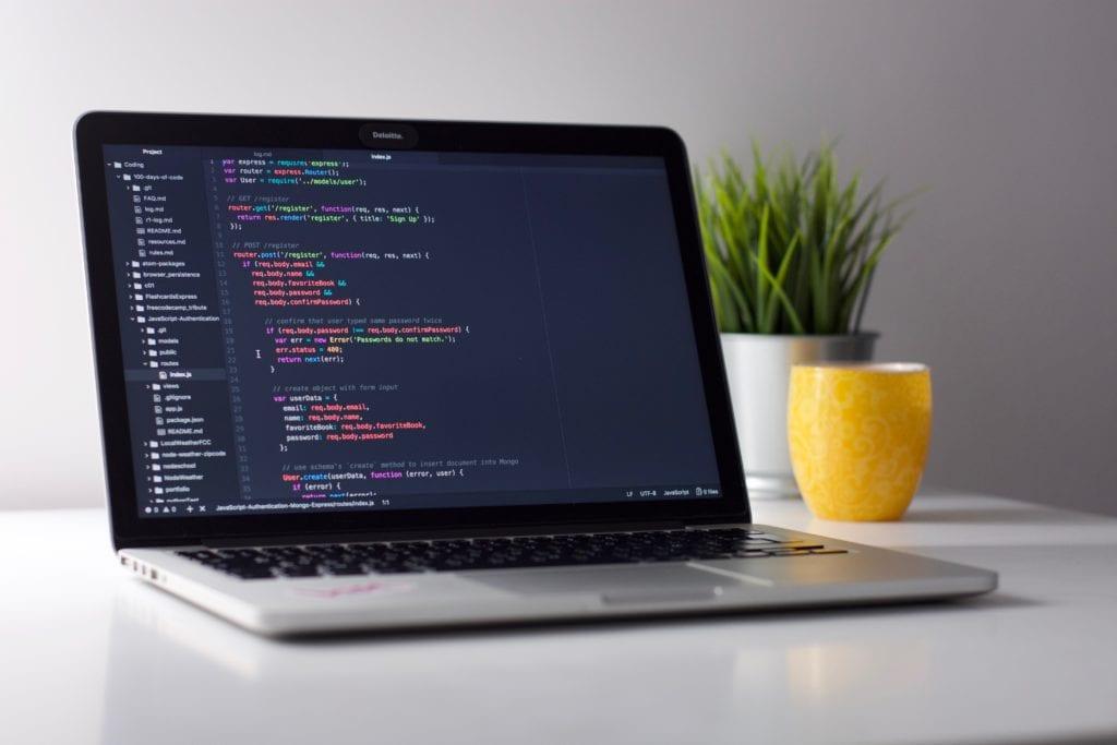 Ordinateur avec des lignes de code montrant le métier de développeur